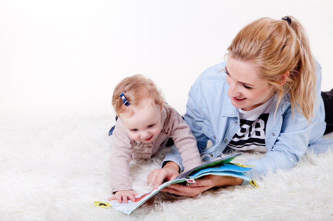Майка показва на детето си книжка с животни