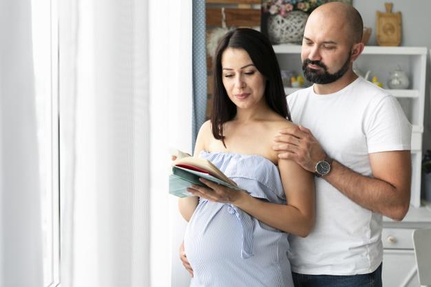 Бременна жена с мъжа си търси име за детето си